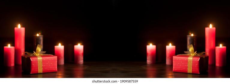 Brennende Kerzen im Dunkeln auf einem Holztisch. Geschenk in einer roten Verpackung und einer goldenen Schleife. Valentinstag. Liebe