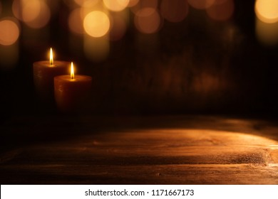 Burning candles in darkness with golden bokeh on wood