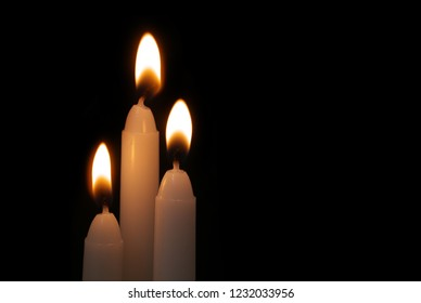 Burning candles in darkness with space for text. Funeral and memorial concept and symbol.