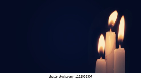 Burning candles in darkness with space for text. Memorial symbol.
