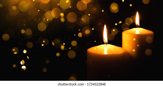 Burning candles with festive bokeh on a black background. Holiday concept.