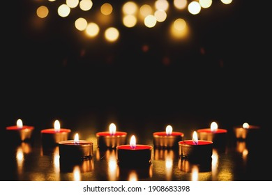 Burning candles with festive bokeh on a black background. Holiday concept. The concept of prayer and hope.