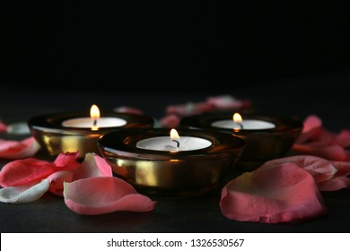 Burning candles with flower petals for celebration of Divaly on dark background