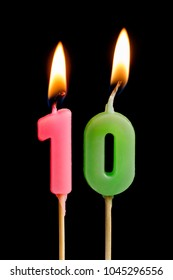 Burning candles in the form of 10 ten figures (numbers, dates) for cake isolated on black background. The concept of celebrating a birthday, anniversary, important date, holiday