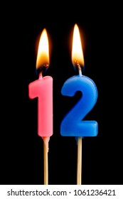 Burning candles in the form of 12 twelve figures (numbers, dates) for cake isolated on black background. The concept of celebrating a birthday, anniversary, important date, holiday, table setting