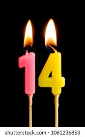 Burning candles in the form of 14 fourteen figures (numbers, dates) for cake isolated on black background. The concept of celebrating a birthday, anniversary, important date, holiday, table setting