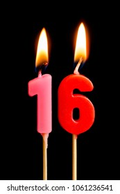 Burning candles in the form of 16 sixteen figures (numbers, dates) for cake isolated on black background. The concept of celebrating a birthday, anniversary, important date, holiday, table setting