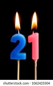 Burning candles in the form of 21 twenty one (numbers, dates) for cake isolated on black background. The concept of celebrating a birthday, anniversary, important date, holiday, table setting