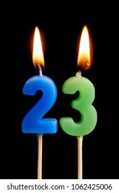 Burning candles in the form of 23 twenty three (numbers, dates) for cake isolated on black background. The concept of celebrating a birthday, anniversary, important date, holiday, table setting