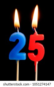 Burning candles in the form of 25 twenty five figures (numbers, dates) for cake isolated on black background. The concept of celebrating a birthday, anniversary, important date, holiday, table setting
