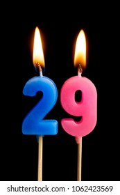 Burning candles in the form of 29 twenty nine (numbers, dates) for cake isolated on black background. The concept of celebrating a birthday, anniversary, important date, holiday, table setting