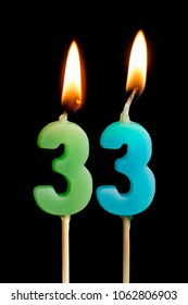 Burning candles in the form of 33 thirty three (numbers, dates) for cake isolated on black background. The concept of celebrating a birthday, anniversary, important date, holiday, table setting