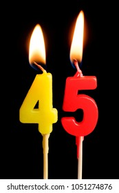 Burning candles in the form of 45 forty five figures (numbers, dates) for cake isolated on black background. The concept of celebrating a birthday, anniversary, important date, holiday, table setting