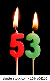 Burning candles in the form of 53 fifty three (numbers, dates) for cake isolated on black background. The concept of celebrating a birthday, anniversary, important date, holiday, table setting