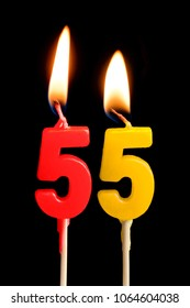 Burning candles in the form of 55 fifty five (numbers, dates) for cake isolated on black background. The concept of celebrating a birthday, anniversary, important date, holiday, table setting