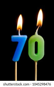 Burning candles in the form of 70 seventy figures (numbers, dates) for cake isolated on black background. The concept of celebrating a birthday, anniversary, important date, holiday