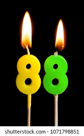 Burning candles in the form of 88 eighty eight (numbers, dates) for cake isolated on black background. The concept of celebrating a birthday, anniversary, important date, holiday, table setting
