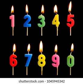 Burning candles in the form of figures (numbers, dates) for cake isolated on black background. The concept of celebrating a birthday, anniversary, important date, holiday, table setting