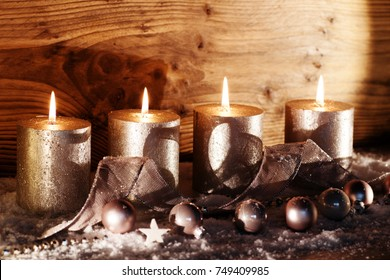 Burning candles in front of a rustic wooden wall for the advent season and christmas