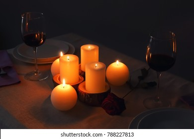 Burning candles and glasses of wine on table in darkness
