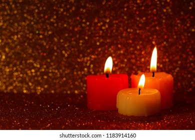Burning candles with the glitter bokeh in the background.