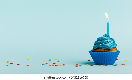 burning candles muffins with star sprinkles against blue backdrop