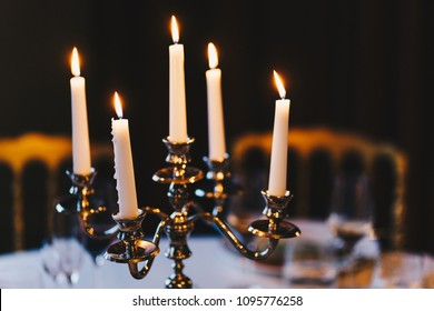 Burning candles on bronze candlestick against dark background at home. Vintage style. Calm romantic atmosphere. Horizontal image for design.