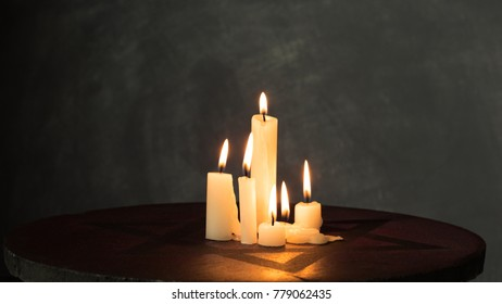 Burning candles on a red-dark stone with the Star of David. A beautiful dark background behind.