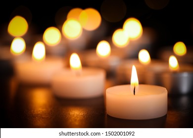 Burning candles on table, closeup. Funeral symbol