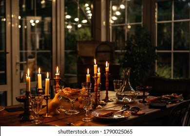 Burning candles on the table in a cozy house in the evening decorate the table with food. Evening romantic dinner at the restaurant.