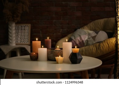Burning candles on table indoors
