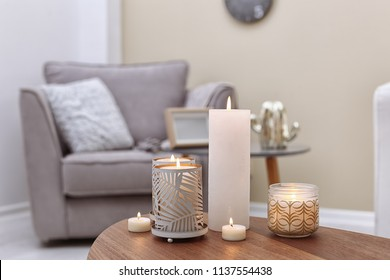 Burning candles on table indoors. Interior decor element