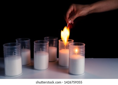 Burning candles on a white background next to the fireworks. Obon festival. Diwali festival. Hand lights candles