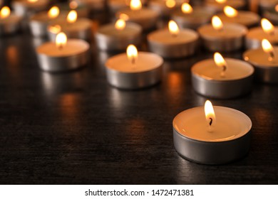 Burning candles on wooden table, space for text. Symbol of sorrow