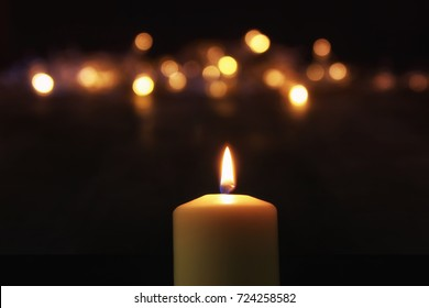 Burning candles over black background with bokeh glitter lights.