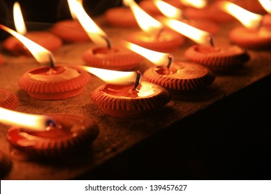 burning candles in sconces on black background