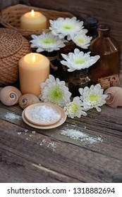 burning candles and sea salt, Spa treatments, relaxation. Beautiful spa composition on rustic wooden background. Spa salon with sea crystal salt, flowers and burning candle.