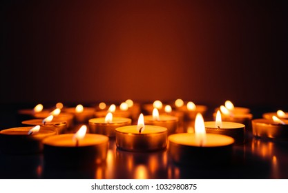 Burning candles. Shallow depth of field. Many christmas candles burning at night. Abstract candles background. Many candle flames glowing on dark background. Close-up. Free space.