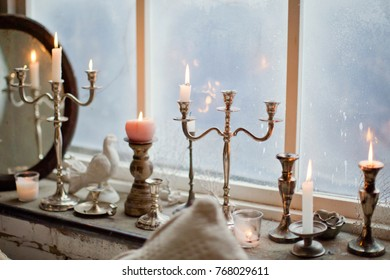 burning candles in silver candlesticks
