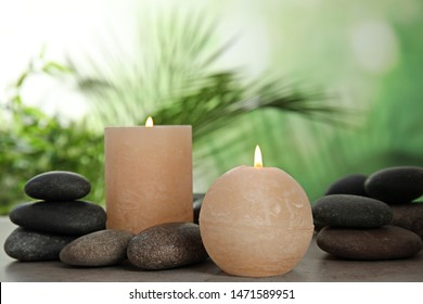 Burning candles and spa stones on table against blurred green background