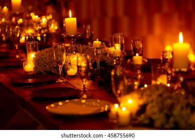 Burning candles and sparkling glasses stand on the rich dinner table