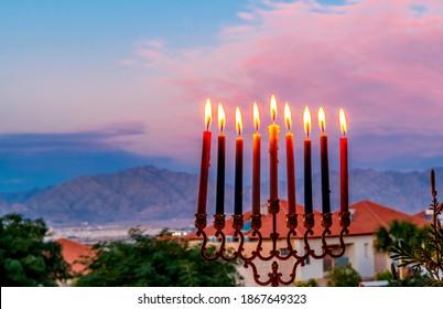Burning candles are traditional symbols of Hanukkah Holiday of light, selective focus on menorah with burning candles, blurred background with colorful sky and mountains during sunset