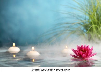 Burning candles and water lily in a serenity pool