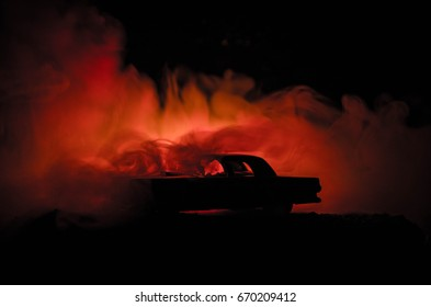 Burning car on a dark background. Car catching fire, after act of vandalism or road indicent. Burning vintage car nightshot