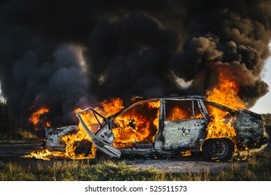 Burning car with open flames and black smoke