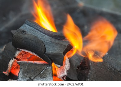 Burning of charcoal grill for BBQ party