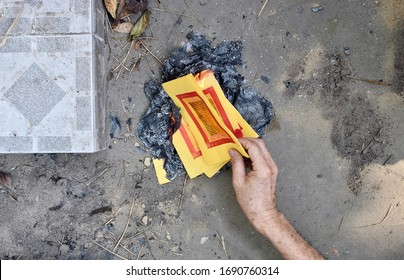 Burning Chinese Joss papers or ghost money  in Chinese New Year or Qingming Festival at Tomb sweeping day in Myanmar or Burma. Day of the dead. First person view.