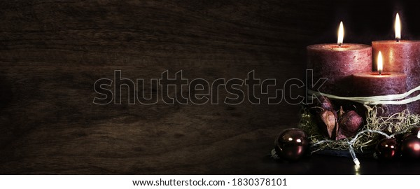 Burning christmas candles on dark wooden background. Symbol for a religious ritual and spiritual meditation or mourning ceremonies. Space for text.