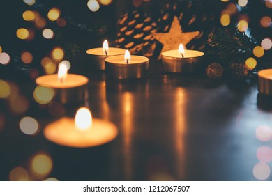 Burning Christmas candles on the table with pine cones, fir branches, decoration star and lights bokeh. Film grain effect added