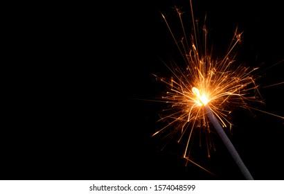 Burning Christmas sparkler on black background